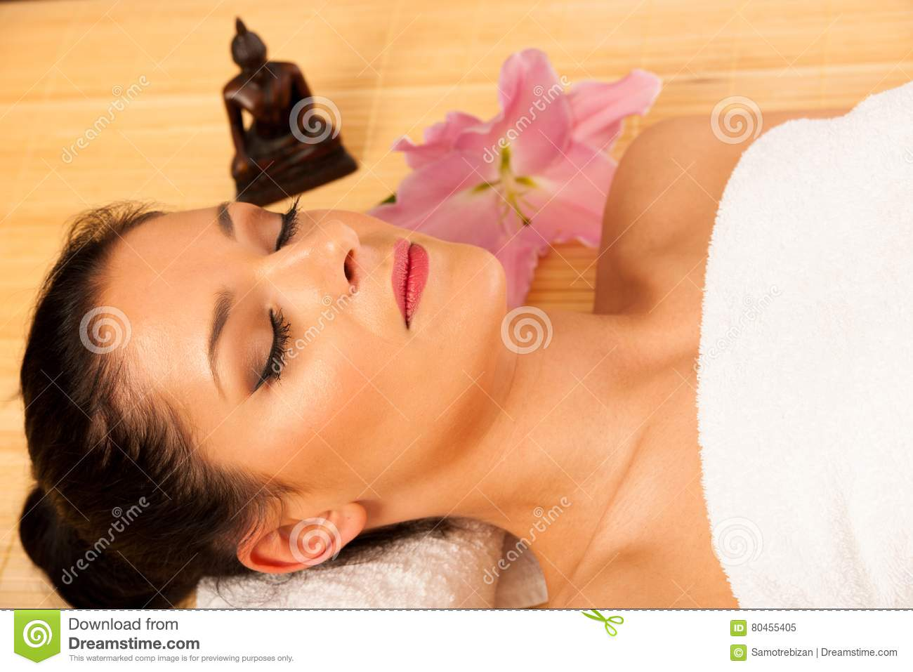 Beautiful young woman having a face massage in wellness studio -