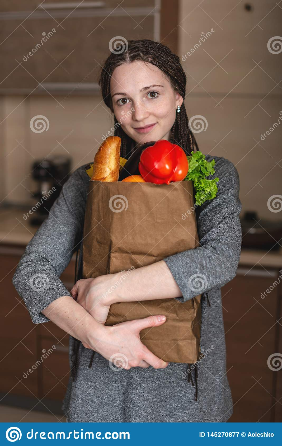 Woman holding full paper bag with products in hands on the background of the kitchen. Healthy and fresh organic food