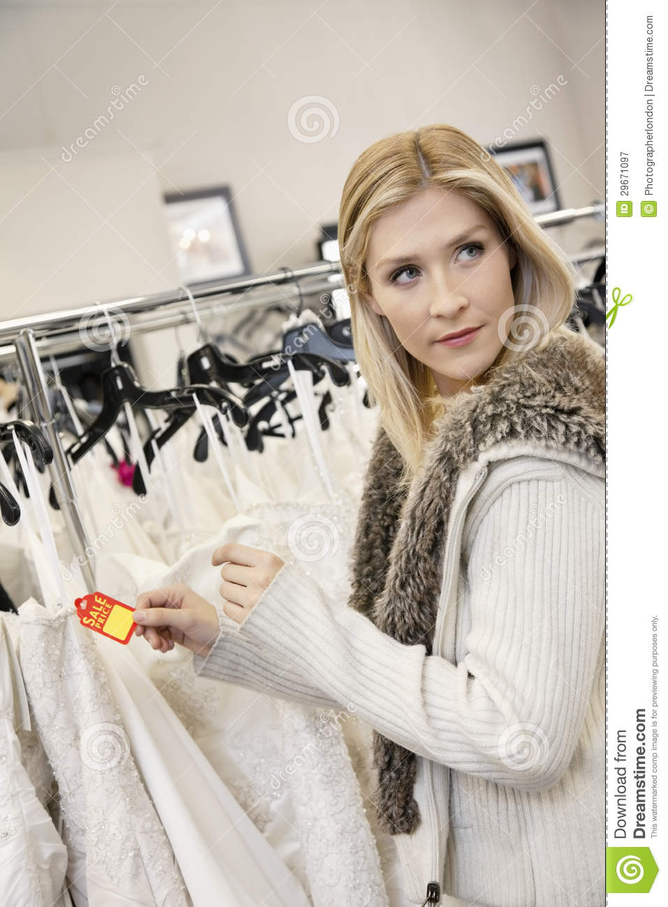 Beautiful Young Woman Holding Price Tag While Looking Away