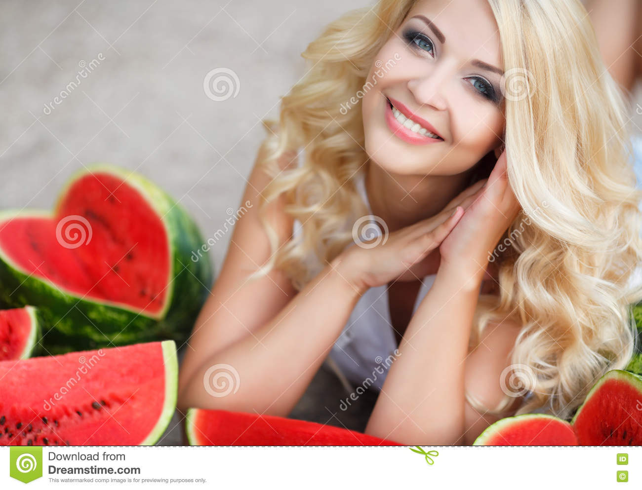 Beautiful young woman holding a slice of ripe watermelon