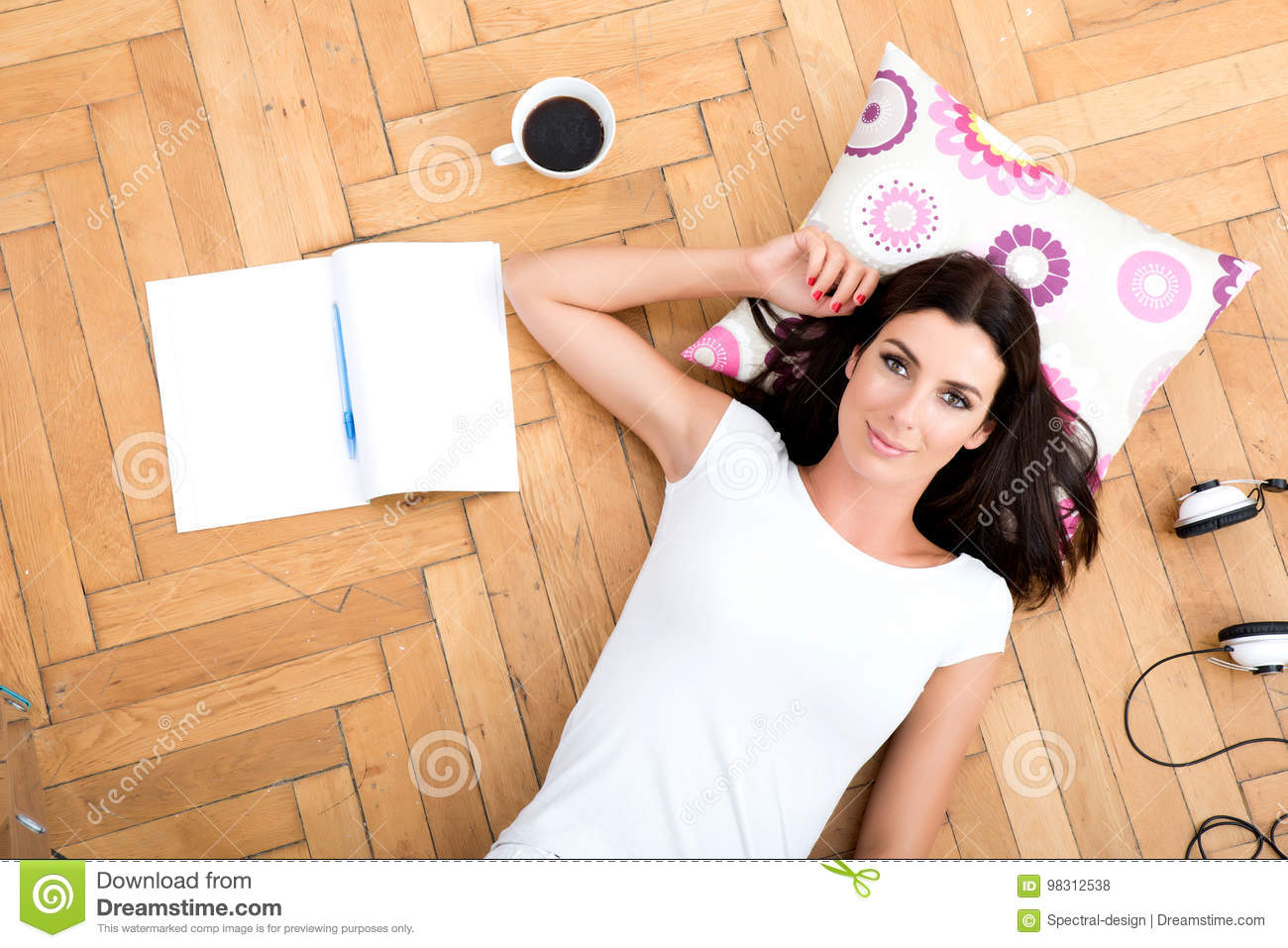 A beautiful young woman laying on the floor, with electronic gad