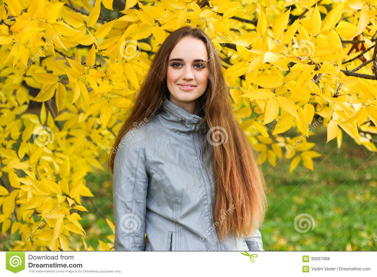 Beautiful young woman in leather jacket and black skirt posing in autumn park.