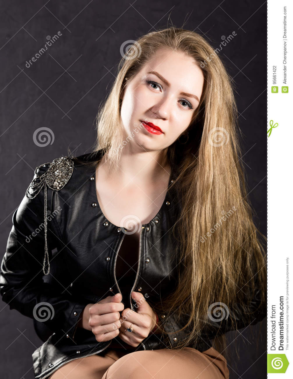 Beautiful young woman in a leather jacket posing on a gray background