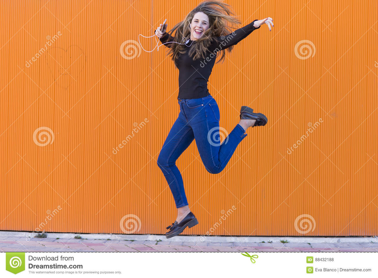Beautiful young woman listening to music with earphones and jump
