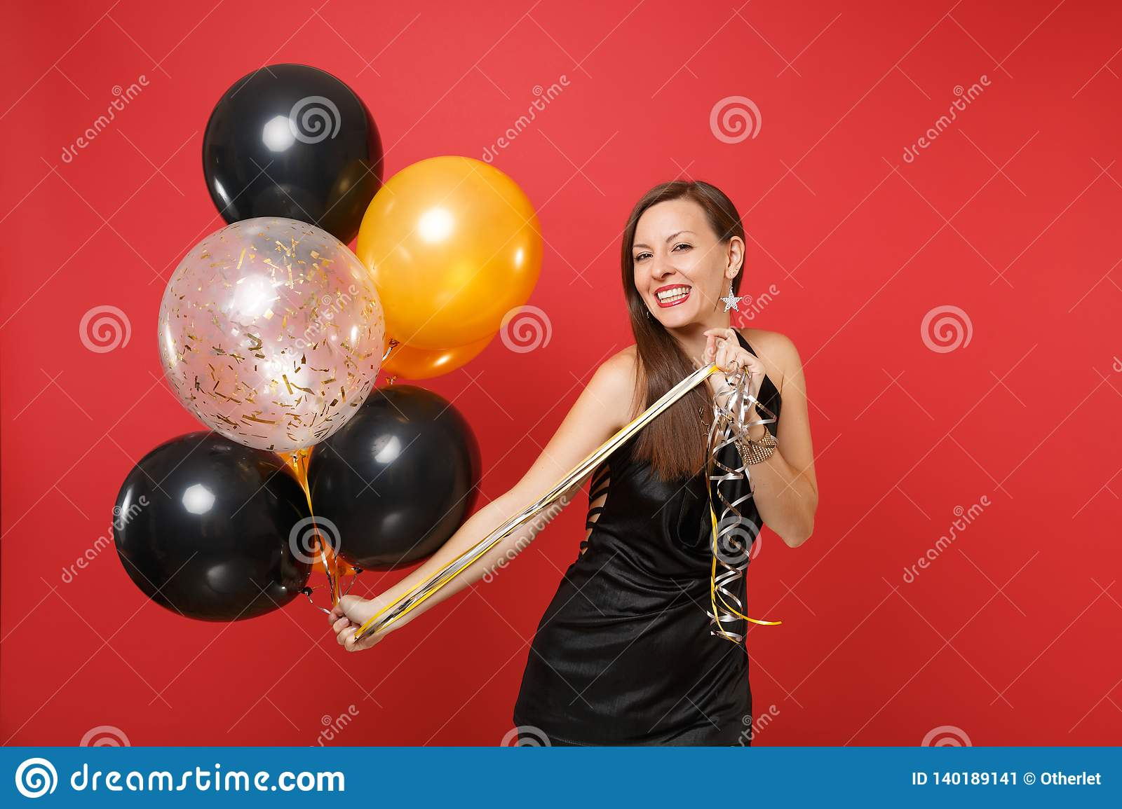 Beautiful young woman in little black dress celebrating holding air balloons isolated on red background. St. Valentine`s