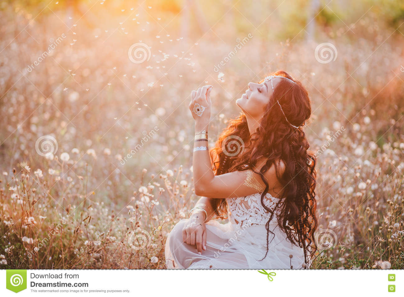 Beautiful young woman with long curly hair dressed in boho style dress posing in a field with dandelions