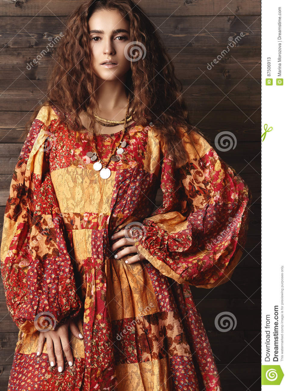 Beautiful young woman with long curly hairstyle, fashion jewelry with brunette hair. Indian style clothes, long dress