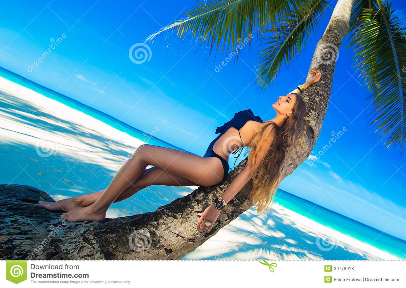Beautiful young woman with long hair relaxing on the palm sea in