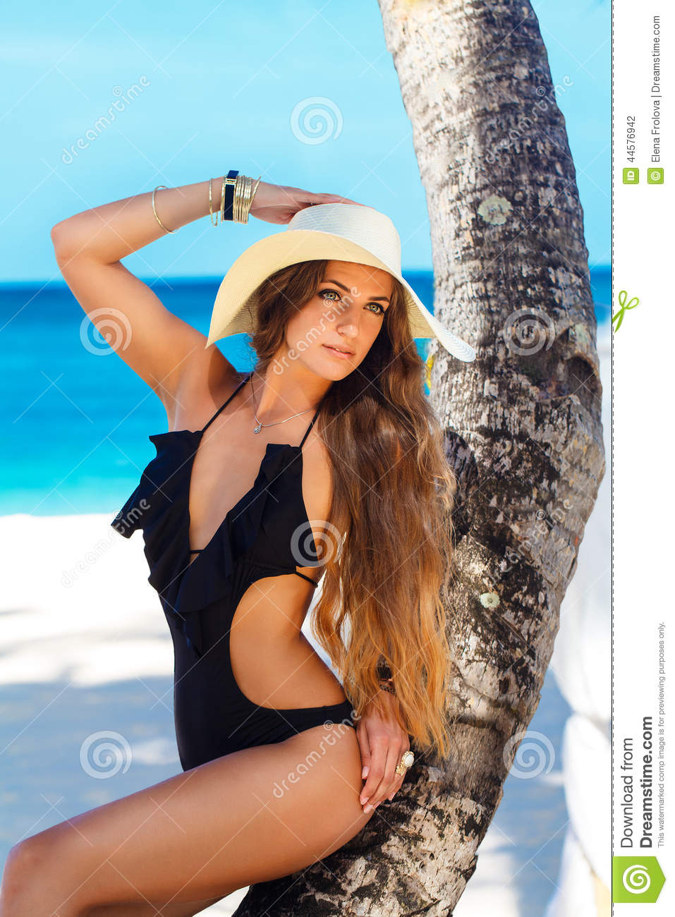 A beautiful young woman with long hair in a straw hat relaxes on