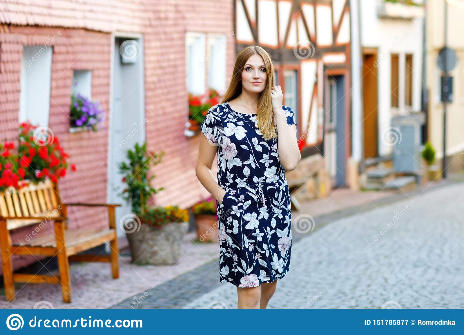 Beautiful young woman with long hairs in summer dress going for a walk in German city. Happy girl enjoying walking in