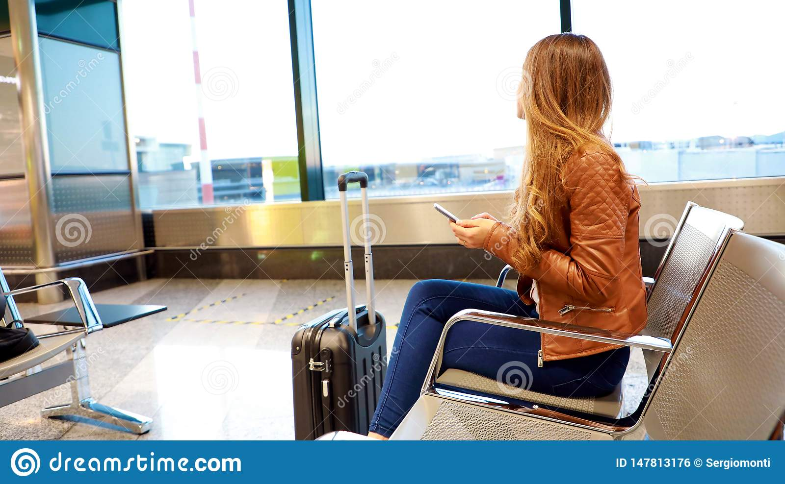 Beautiful young woman looking out window at flying airplane while waiting boarding on aircraft in airport lounge