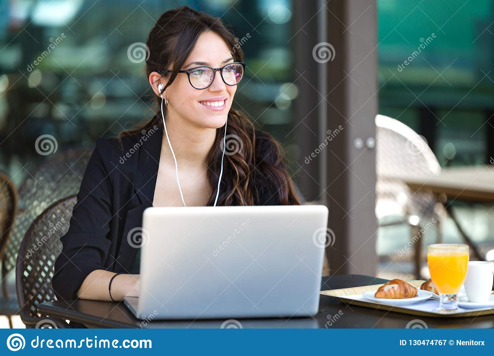 Beautiful young woman looking sideways while working with her laptop in a coffee shop.