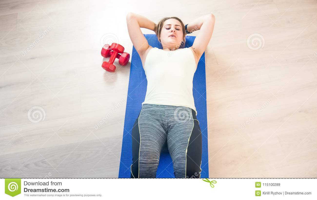 Beautiful Young Woman Lying On Fitness Mat And Doing Abs Sit