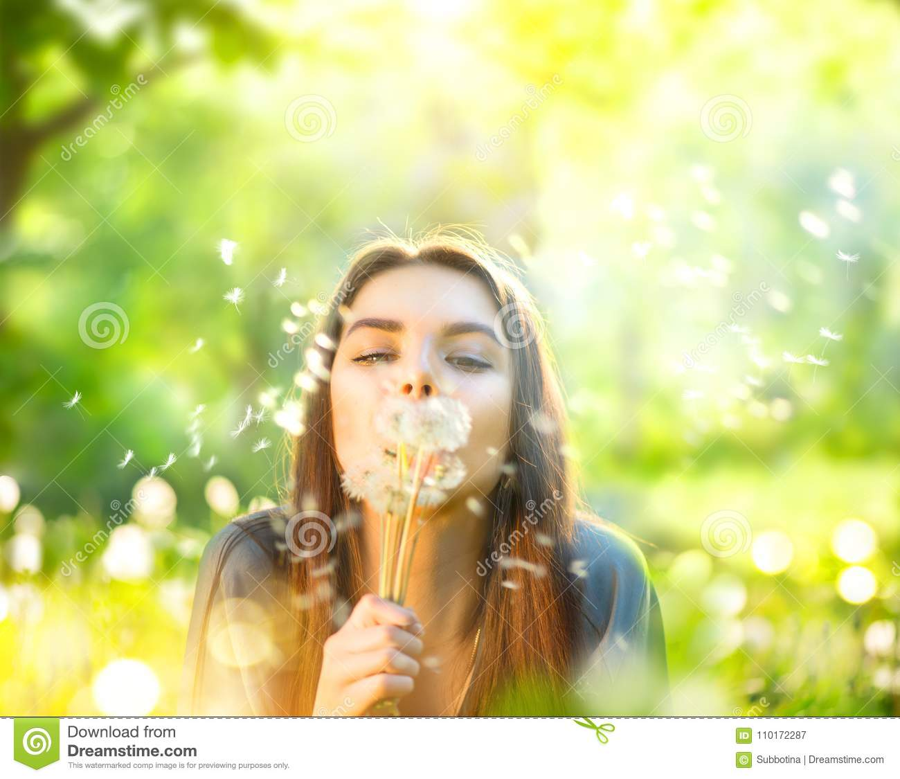 Beautiful young woman lying on green grass and blowing dandelions