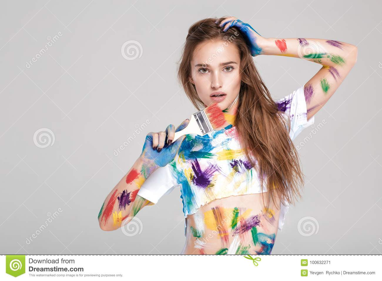 Young woman smeared in multicolored paint.
