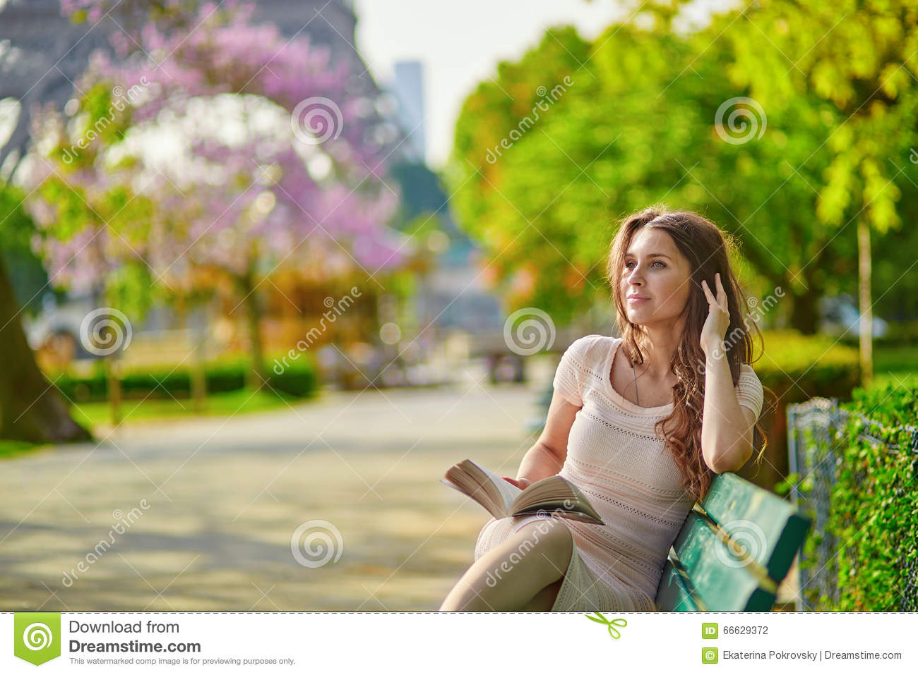 Beautiful young woman in Paris reading on the bench outdoors