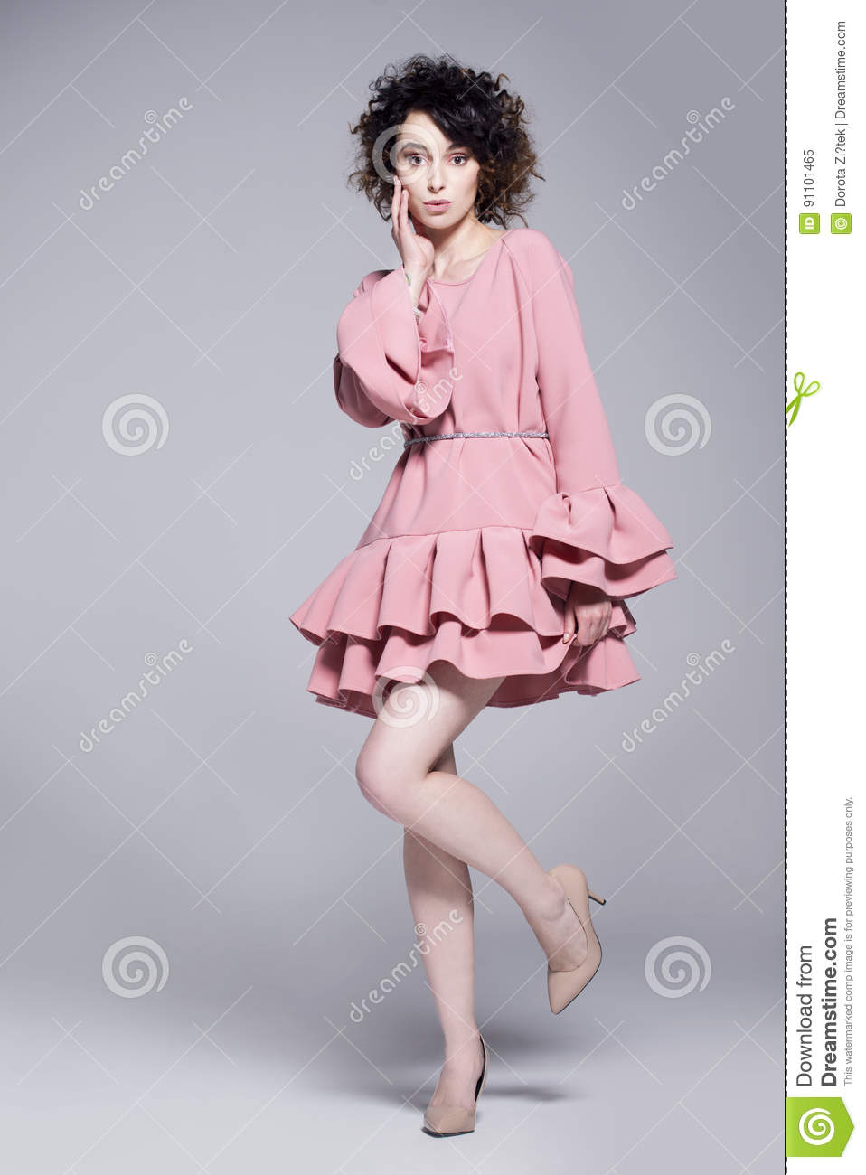 Beautiful young woman in a pink dress with frills