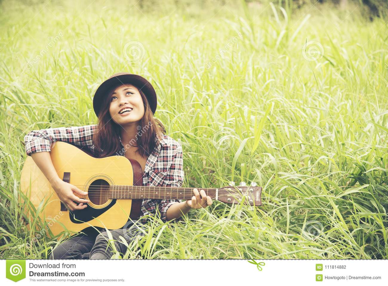 Beautiful young woman playing guitar on the green meadow.