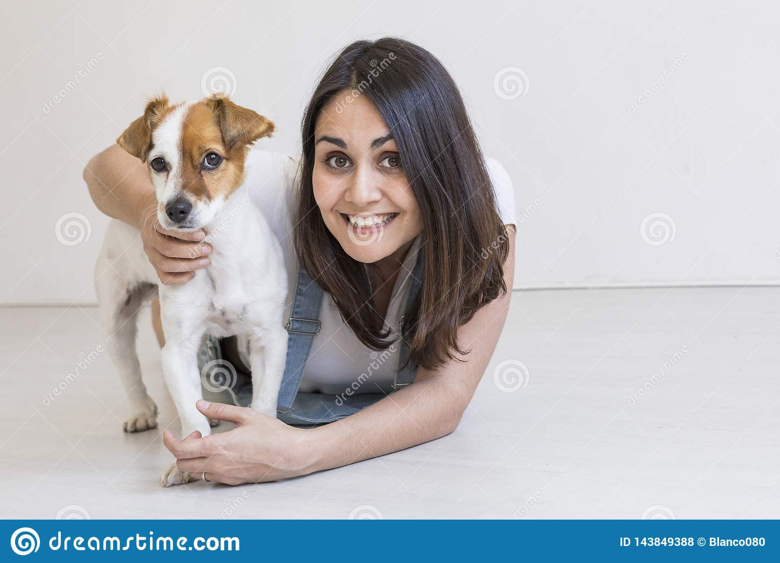 Beautiful young woman playing with her little cute dog at home. Lifestyle portrait. Love for animals concept. white background