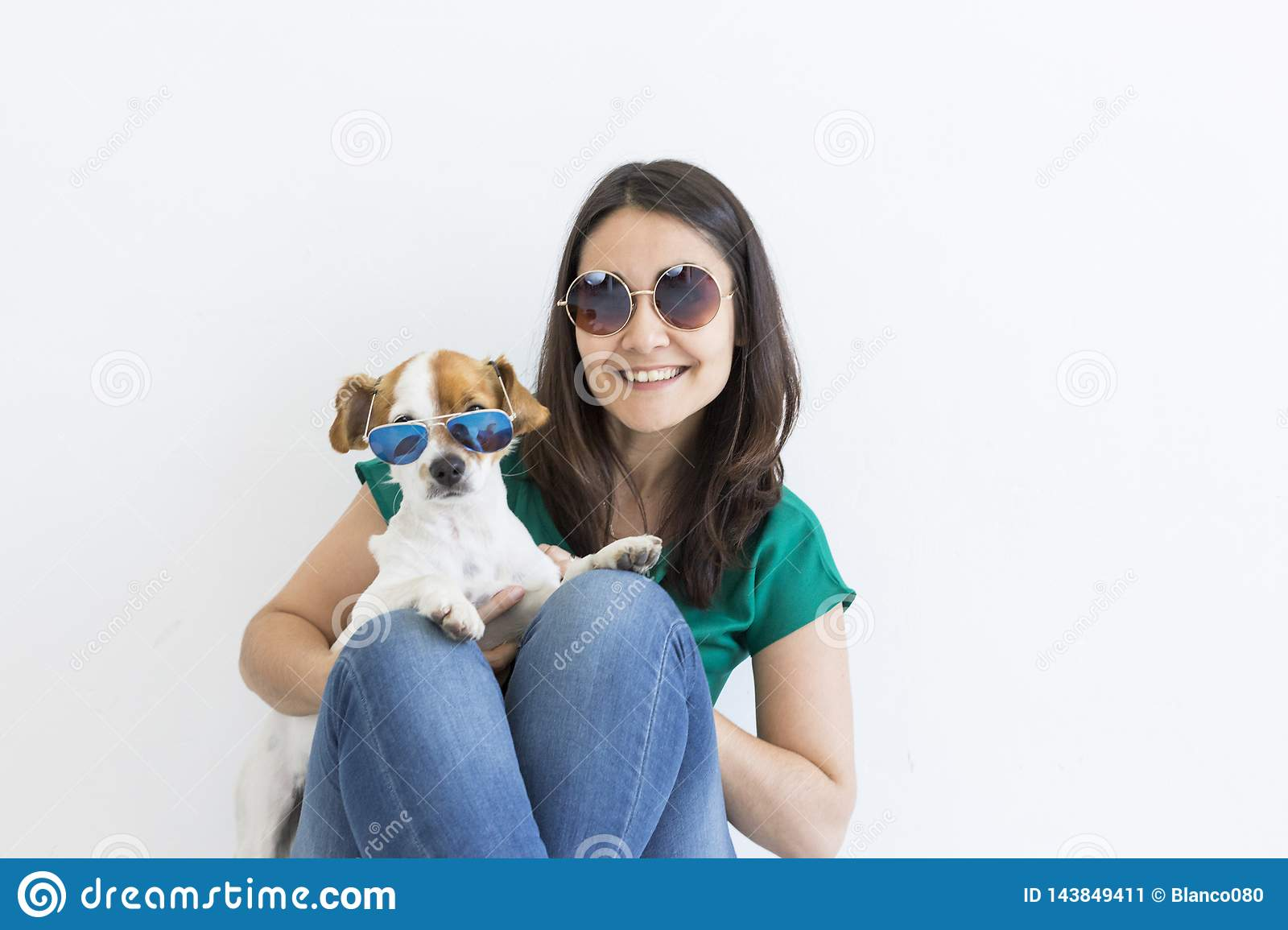 Beautiful young woman playing with her little cute dog at home. Lifestyle portrait. Love for animals concept. white background.