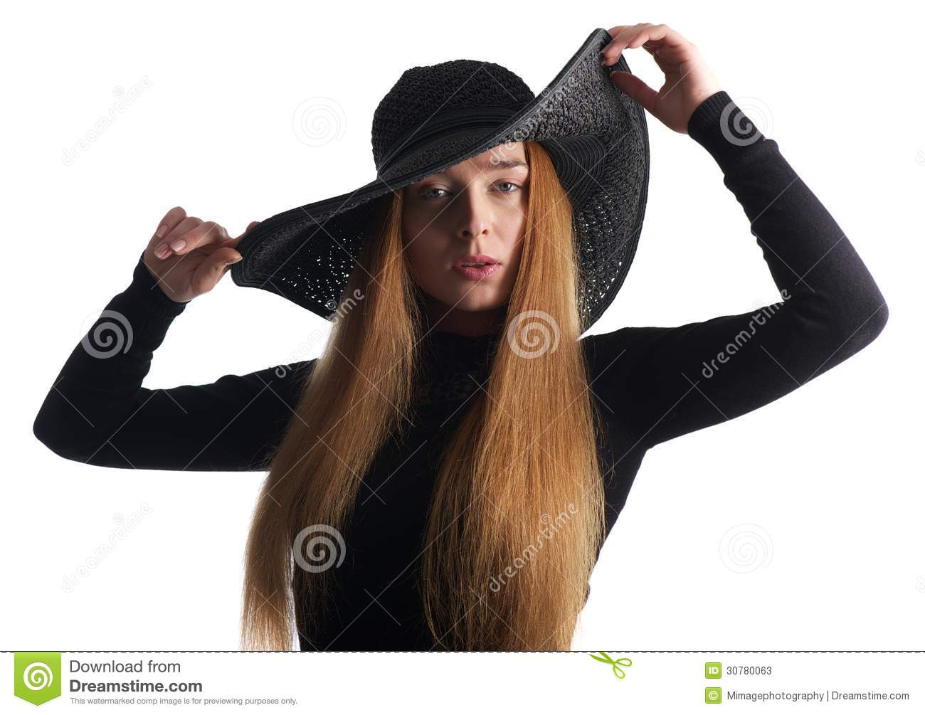 Beautiful young woman posing in black hat isolated on white