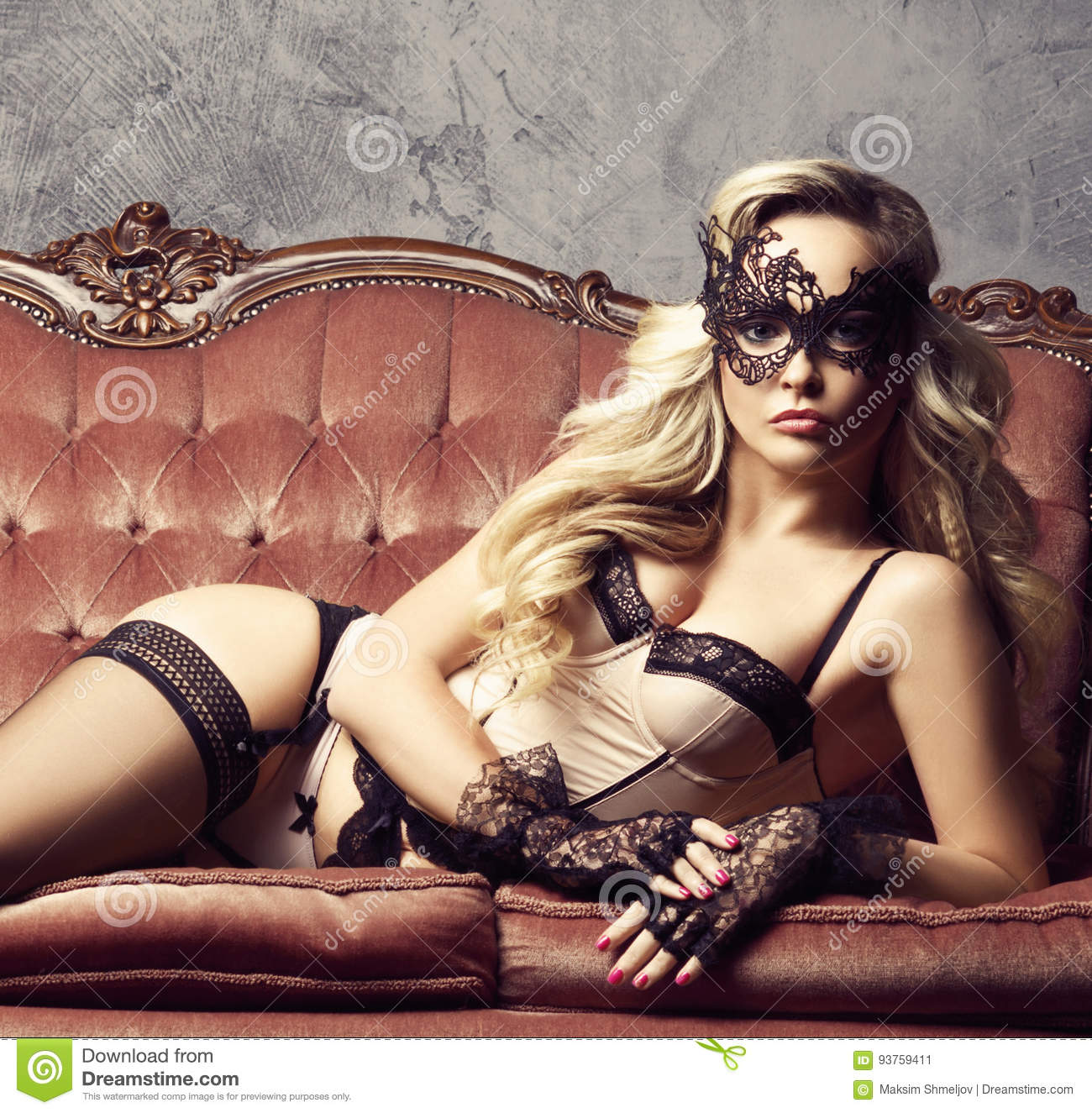 84d3a1f5f81 Beautiful and young woman posing in lingerie and Venetian mask on red sofa.  Vintage interior and retro background.