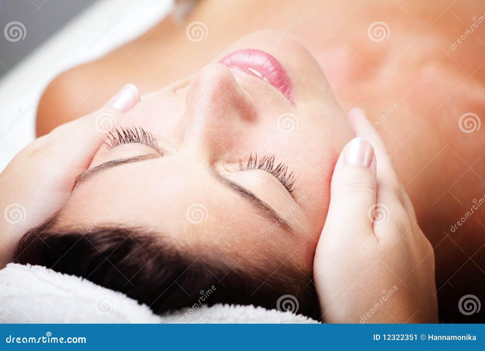Beautiful young woman receiving facial massage.