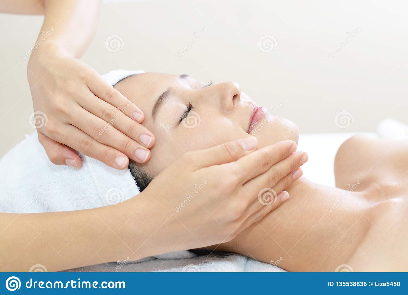 Beautiful young woman receiving facial massage