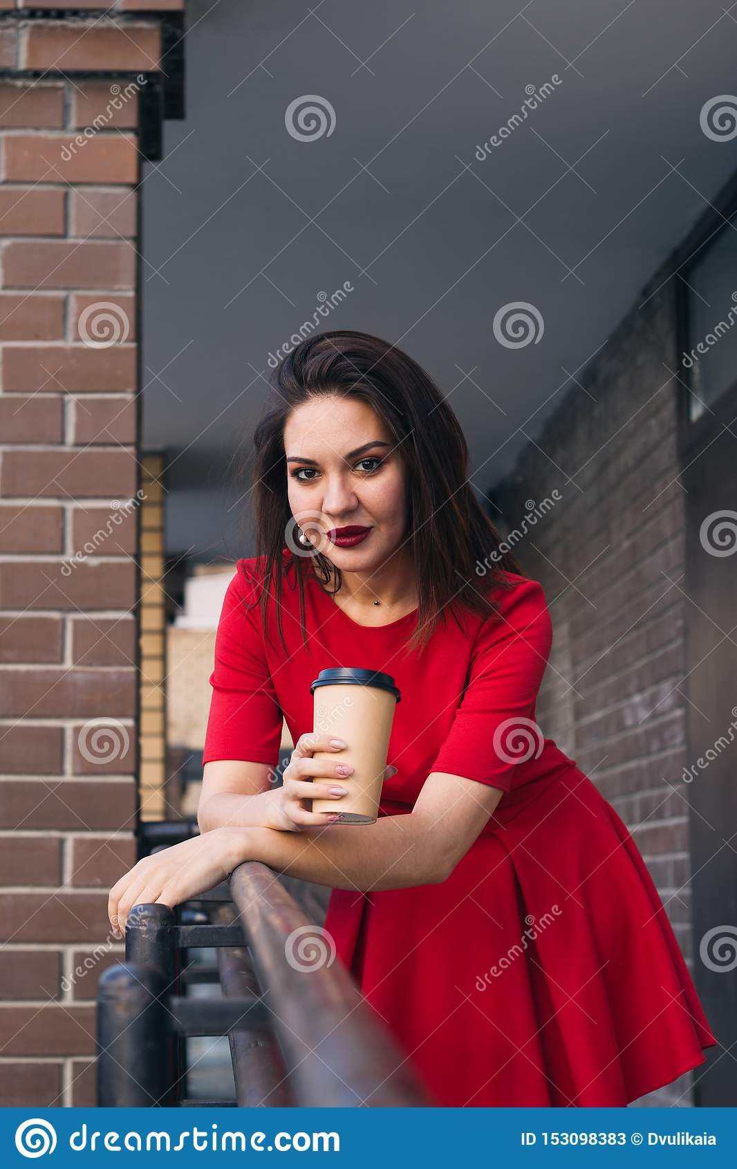 beautiful young woman with red lipstick in red dress holding takeaway cup of drink on the street