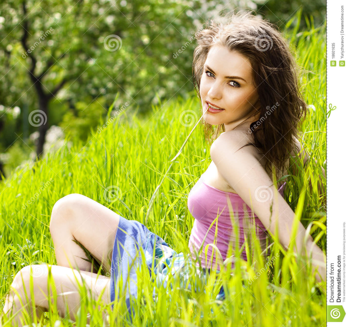 Beautiful Young Woman Relaxing In The Grass Stock Image