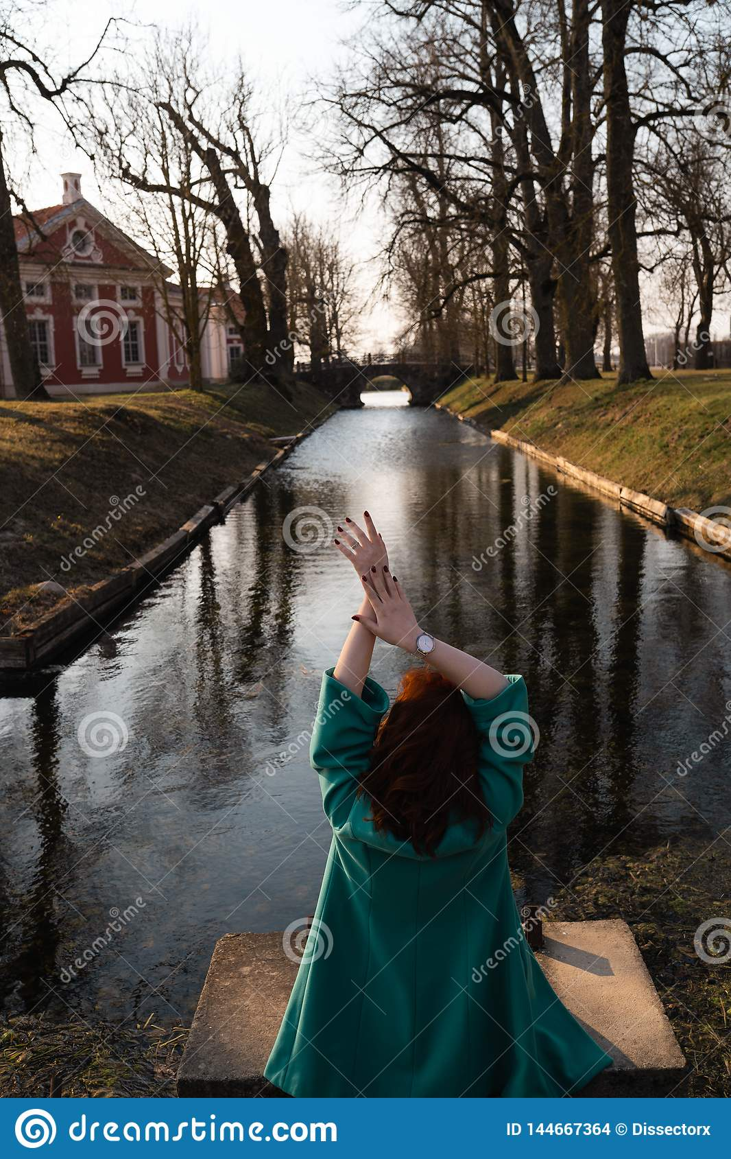 Beautiful young woman relaxing near a canal river in a park near the palace in Rundale, Latvia, 2019