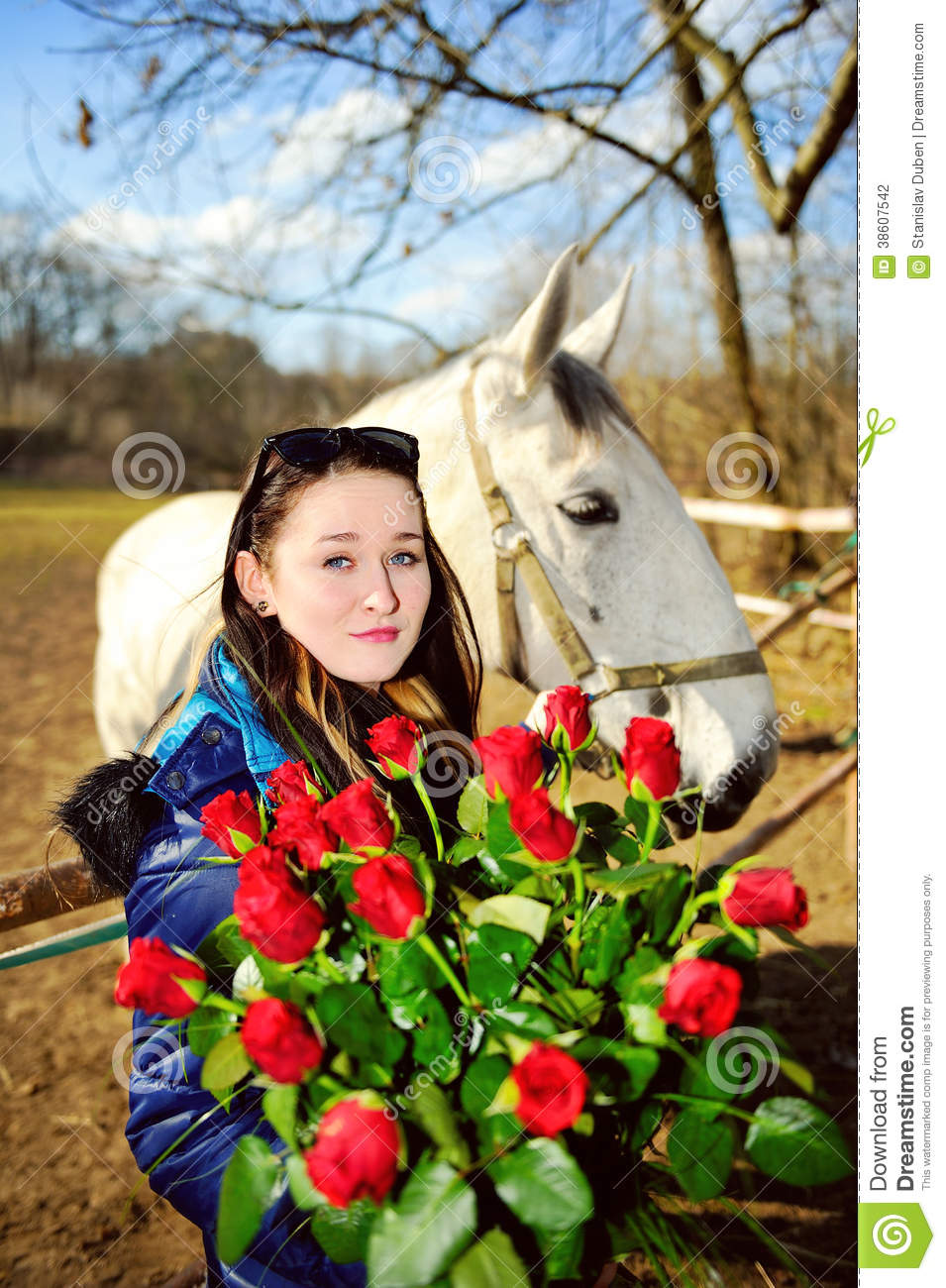 Beautiful young woman with roses and white horse