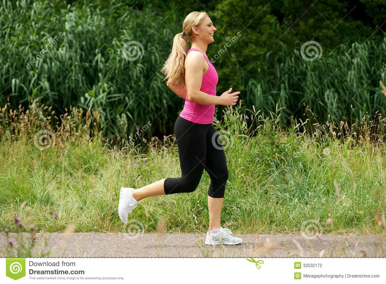 beautiful young woman running in the park stock photo