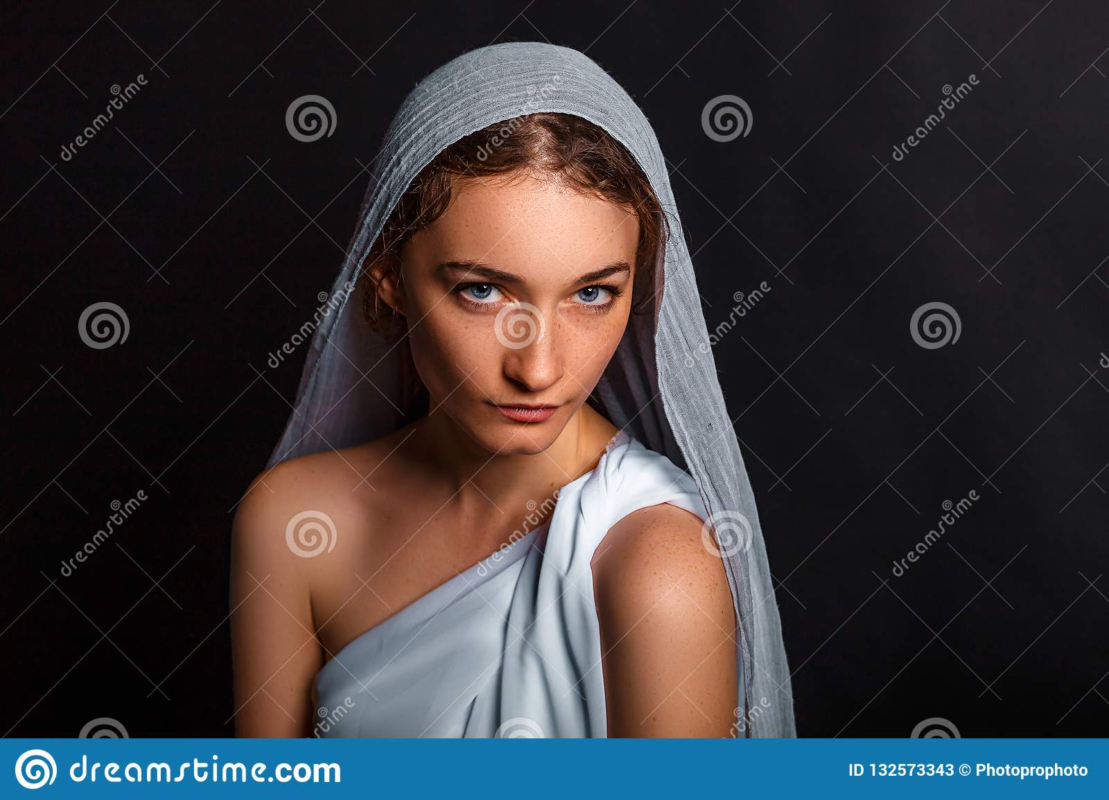 Beautiful young woman with a scarf on her head, and a rosary in her hands, humble look, believing woman