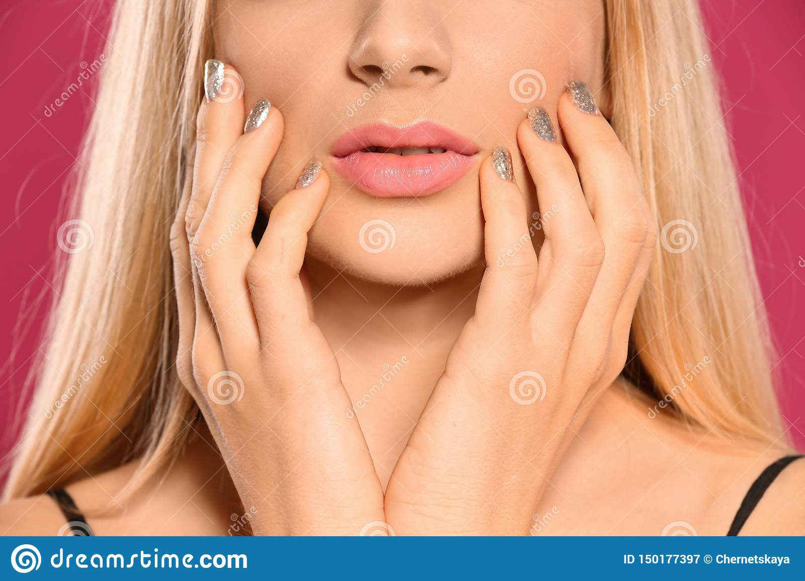 Beautiful young woman with shiny manicure on color background. Nail polish trends