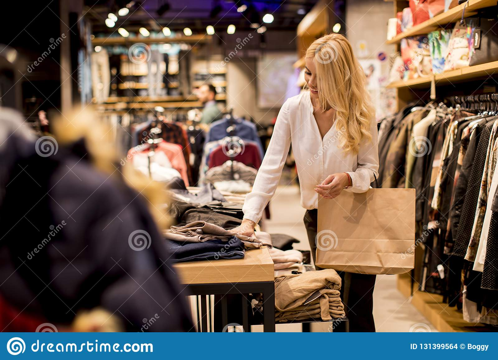 d4011376c3 Beautiful Young Woman With Shopping Bags Standing At Clothing Store ...