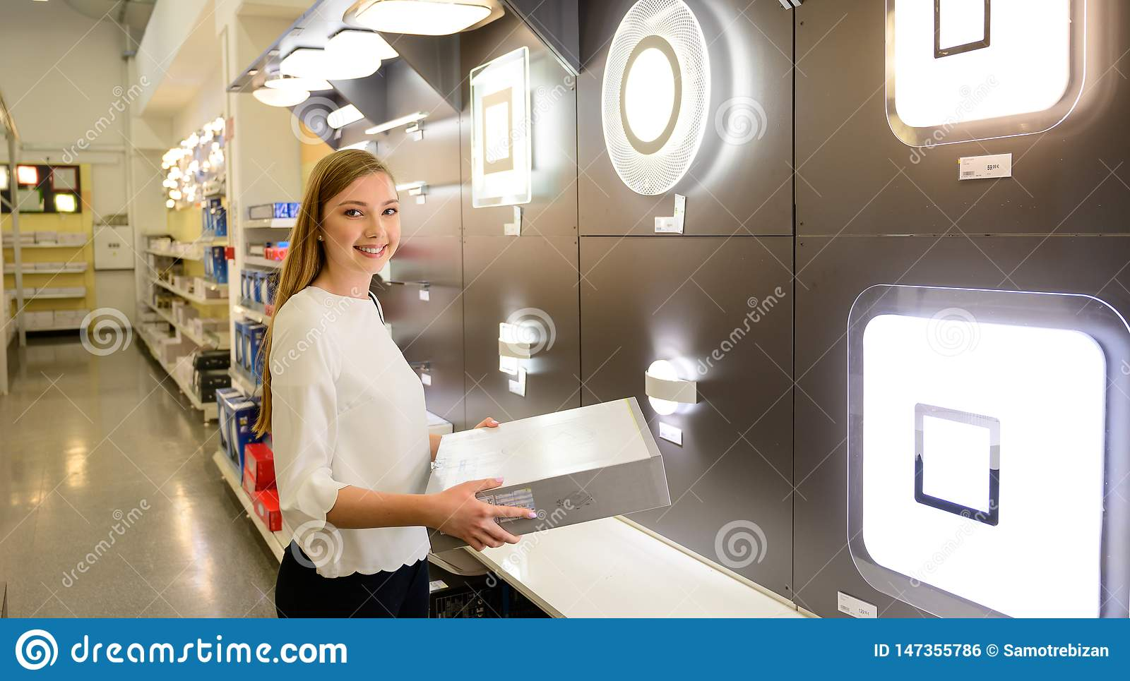 Beautiful young woman shopping chandelier lights fro her home