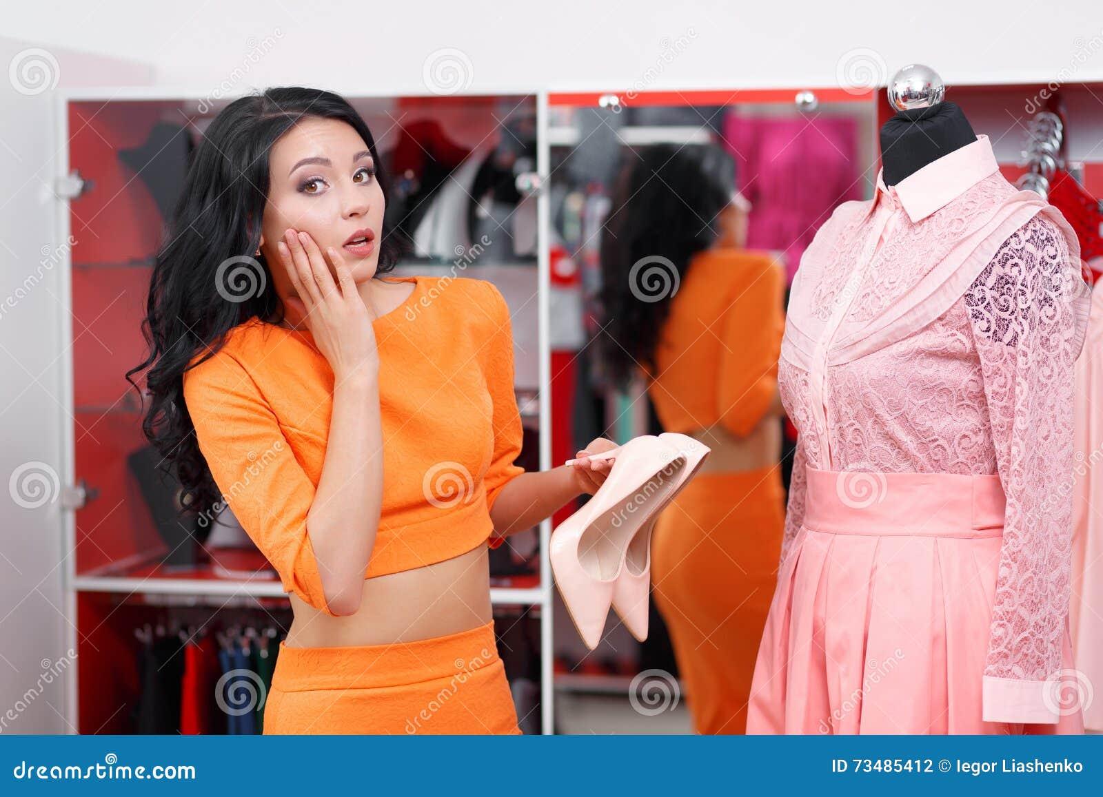c60b21a1ea594 Young woman shopping in a clothing store. Caucasian shopper girl choosing  pink dress in shop during sale. Woman shopping for dress. Fashion shopping