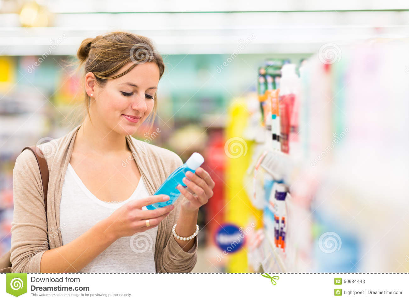 Beautiful young woman shopping for cosmetics in a grocery store