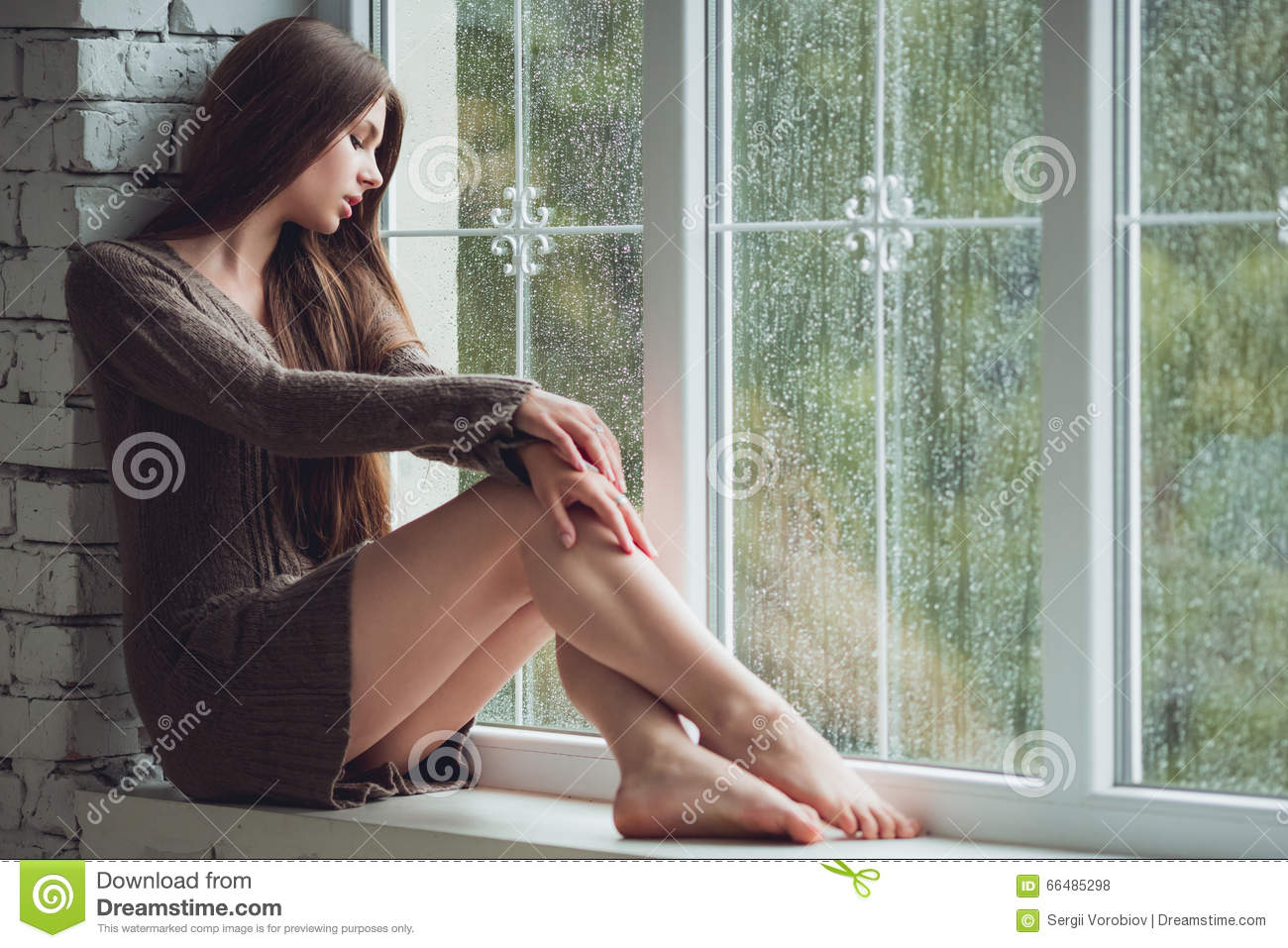 Beautiful young woman sitting alone near window with rain drops. and sad girl. Concept of loneliness