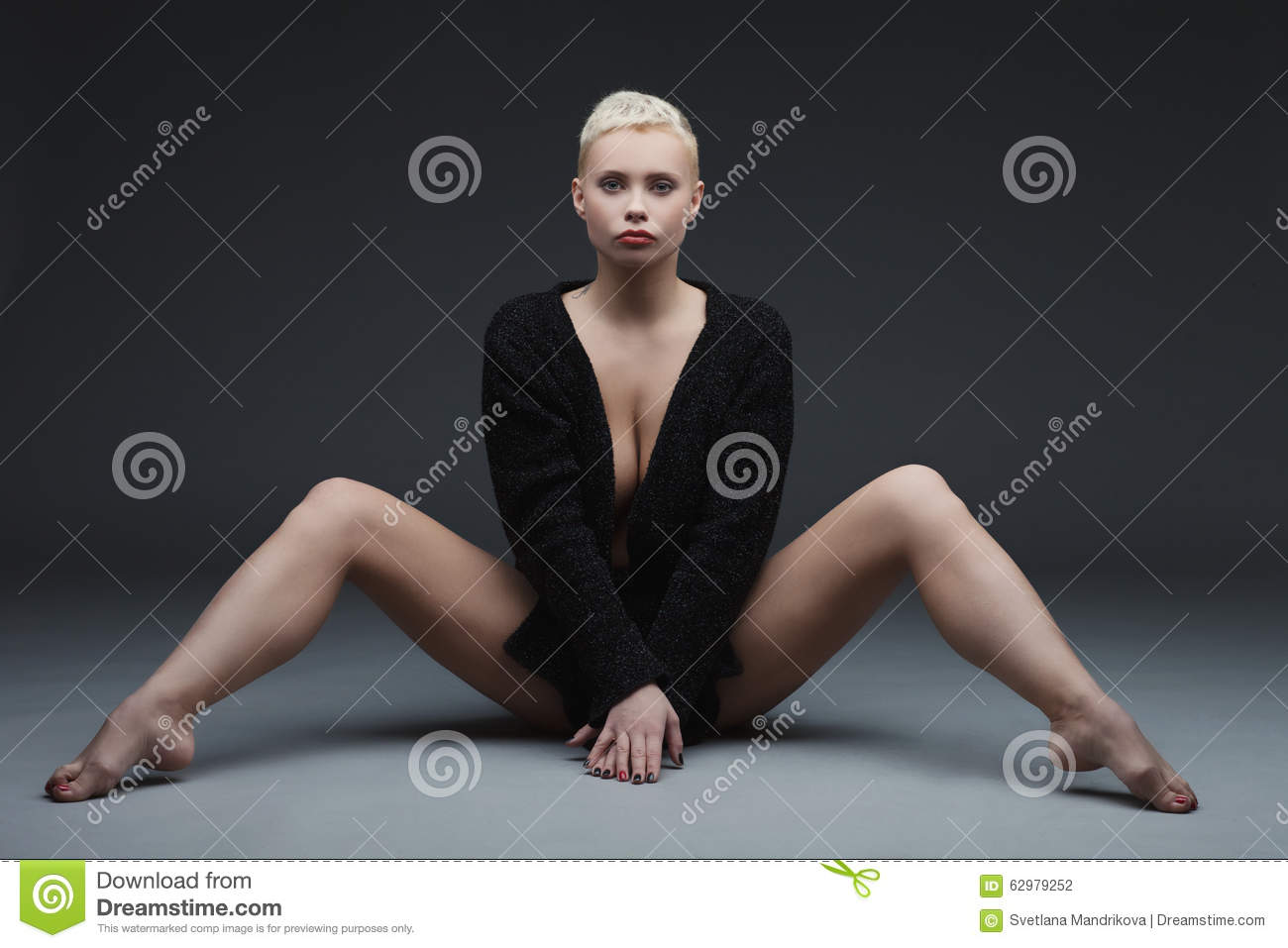 beautiful young woman sitting with legs spread stock photo - image