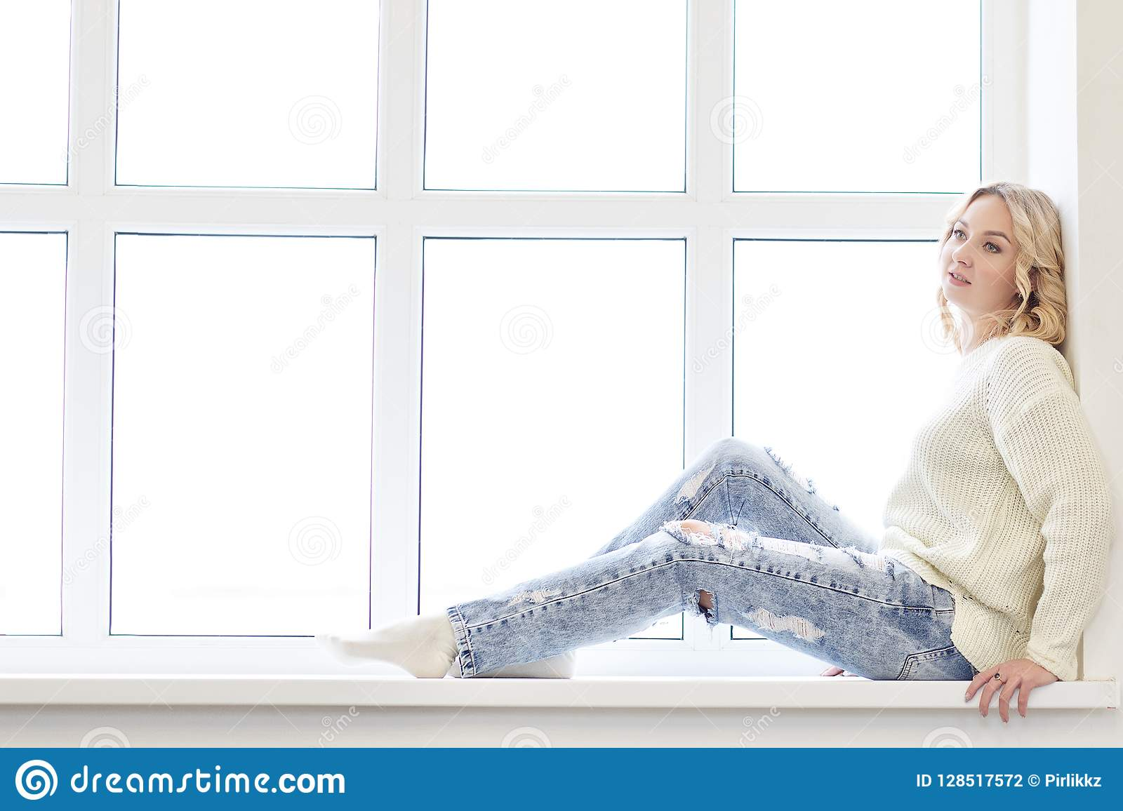 Young woman sitting in front of window.