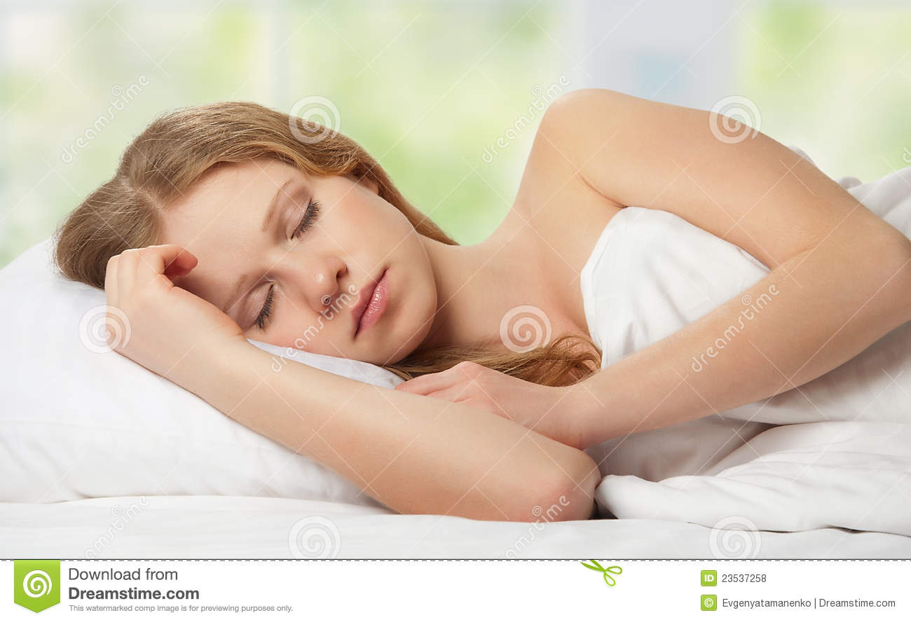Beautiful young woman sleeping in bed against the window with the ...