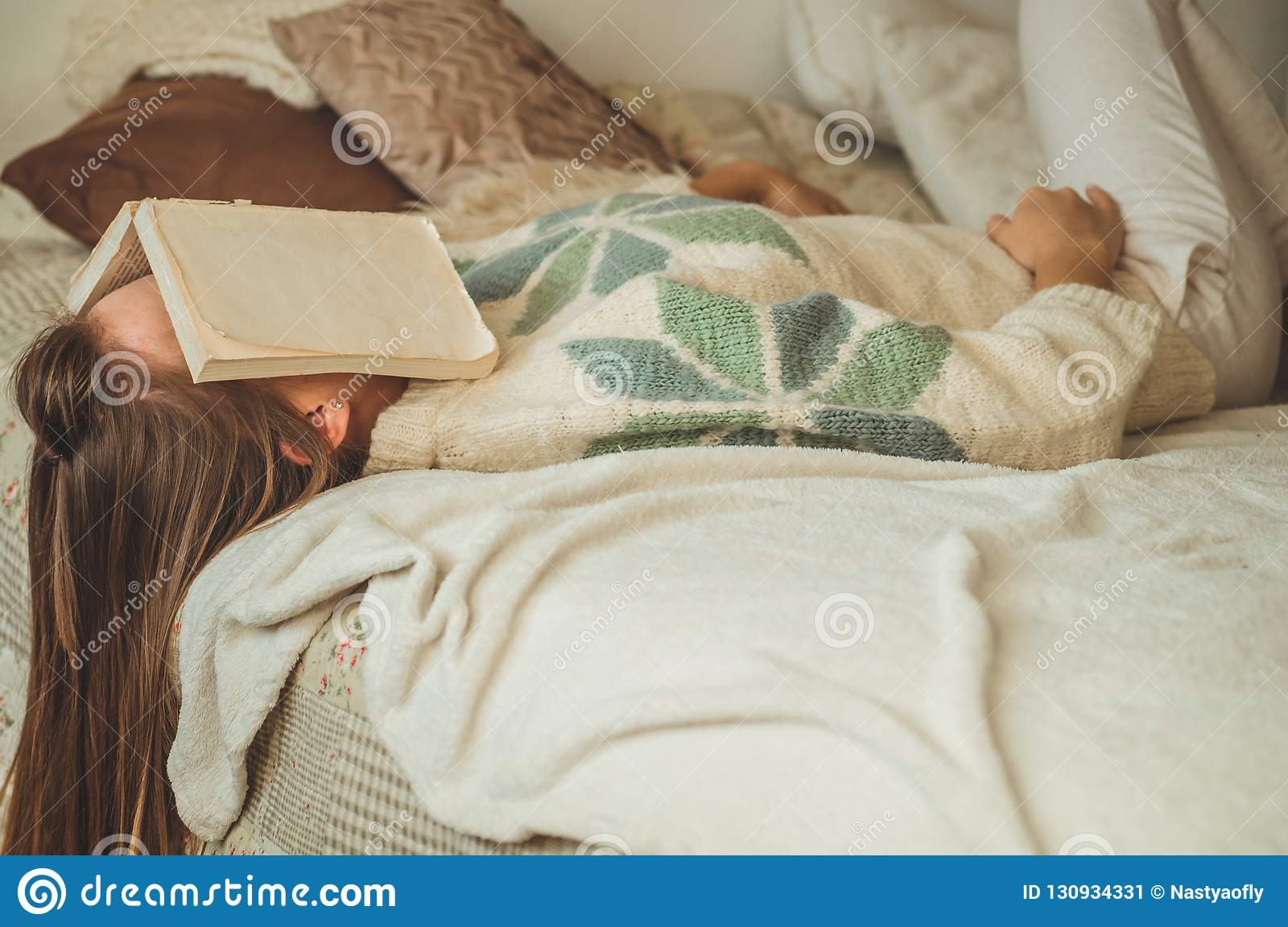 Beautiful young woman sleeping on bed with book covering her face because reading book with preparing exam of college