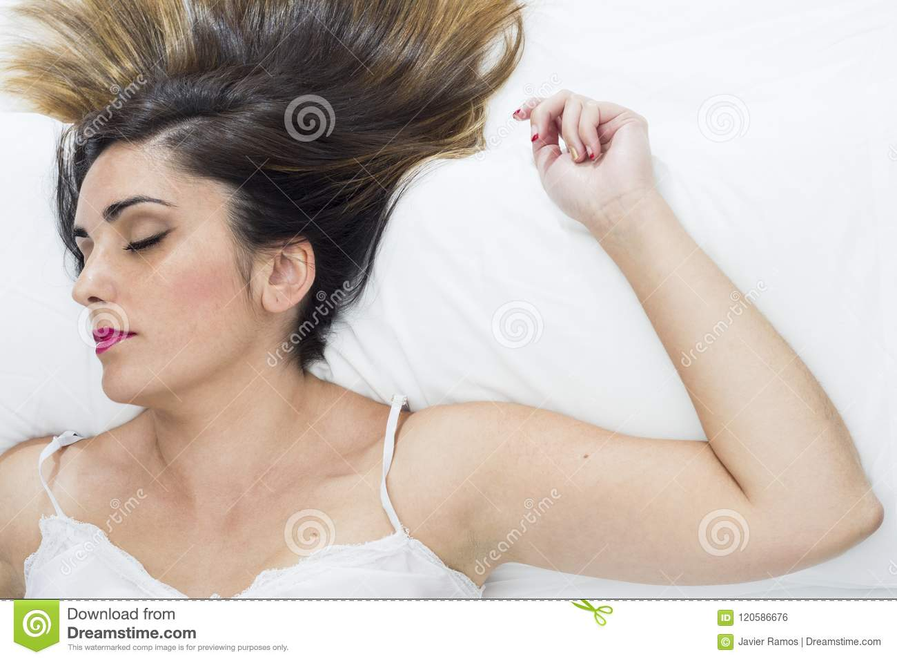 7362ded1db Beautiful young woman sleeping very relaxed on a white bed with a white  nightgown.