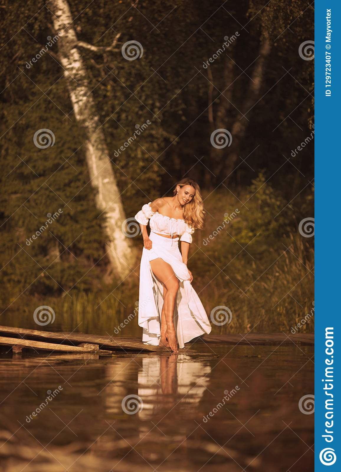 Beautiful young woman standing by the lake showing her legs