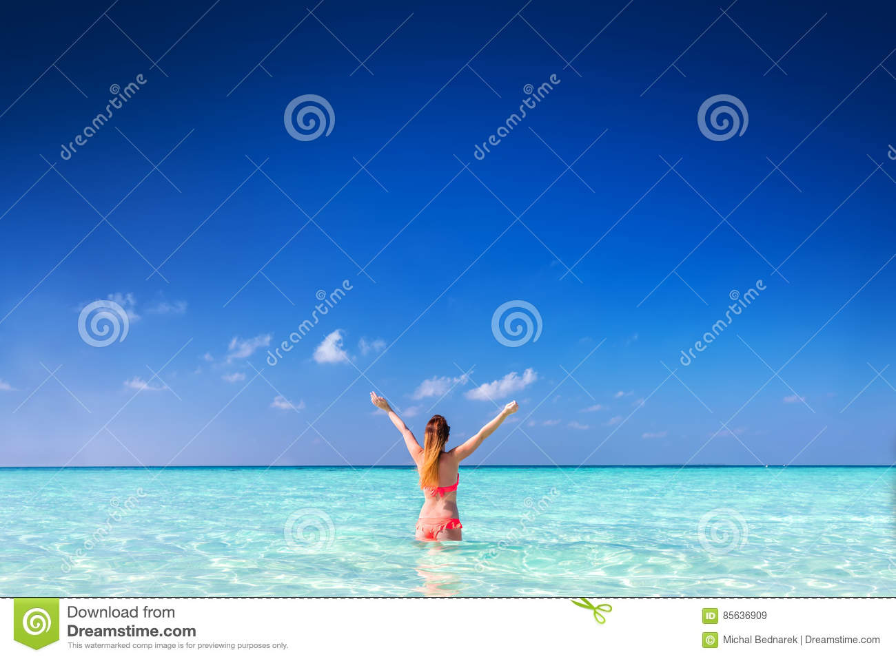 Beautiful young woman standing in the ocean with hands raised. Maldives