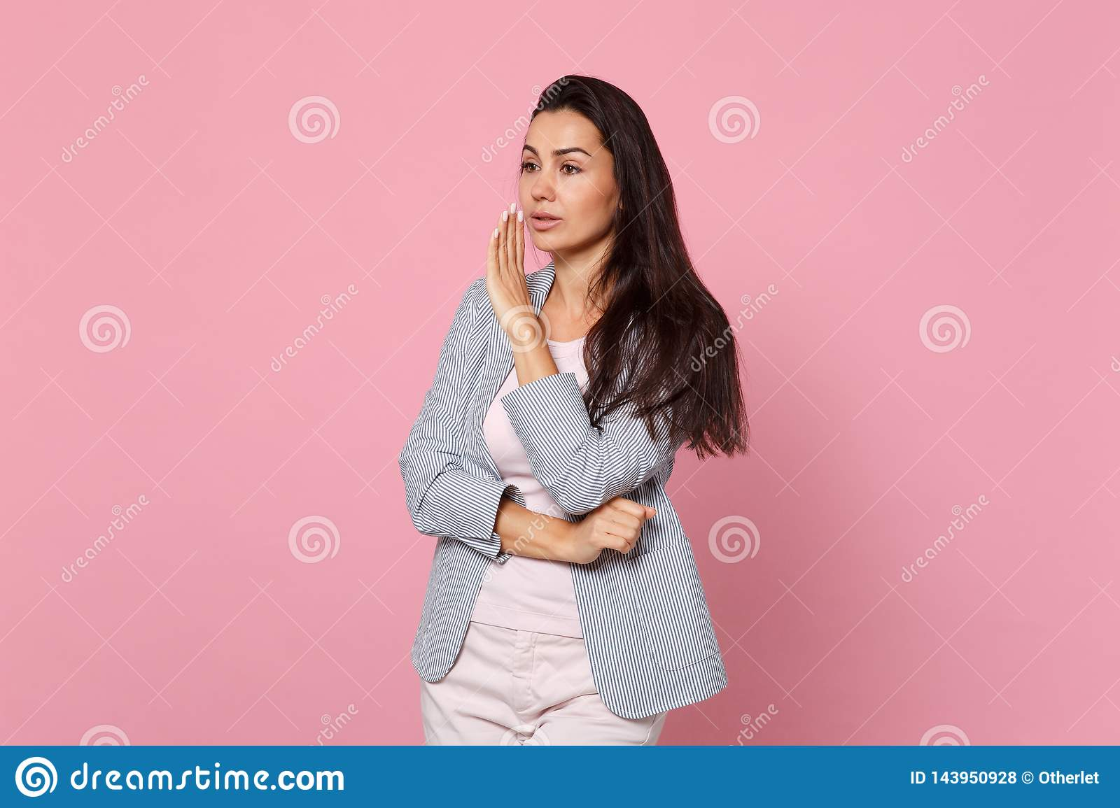 Beautiful young woman in striped jacket looking aside whispers gossip tells secret with hand gesture isolated on pink
