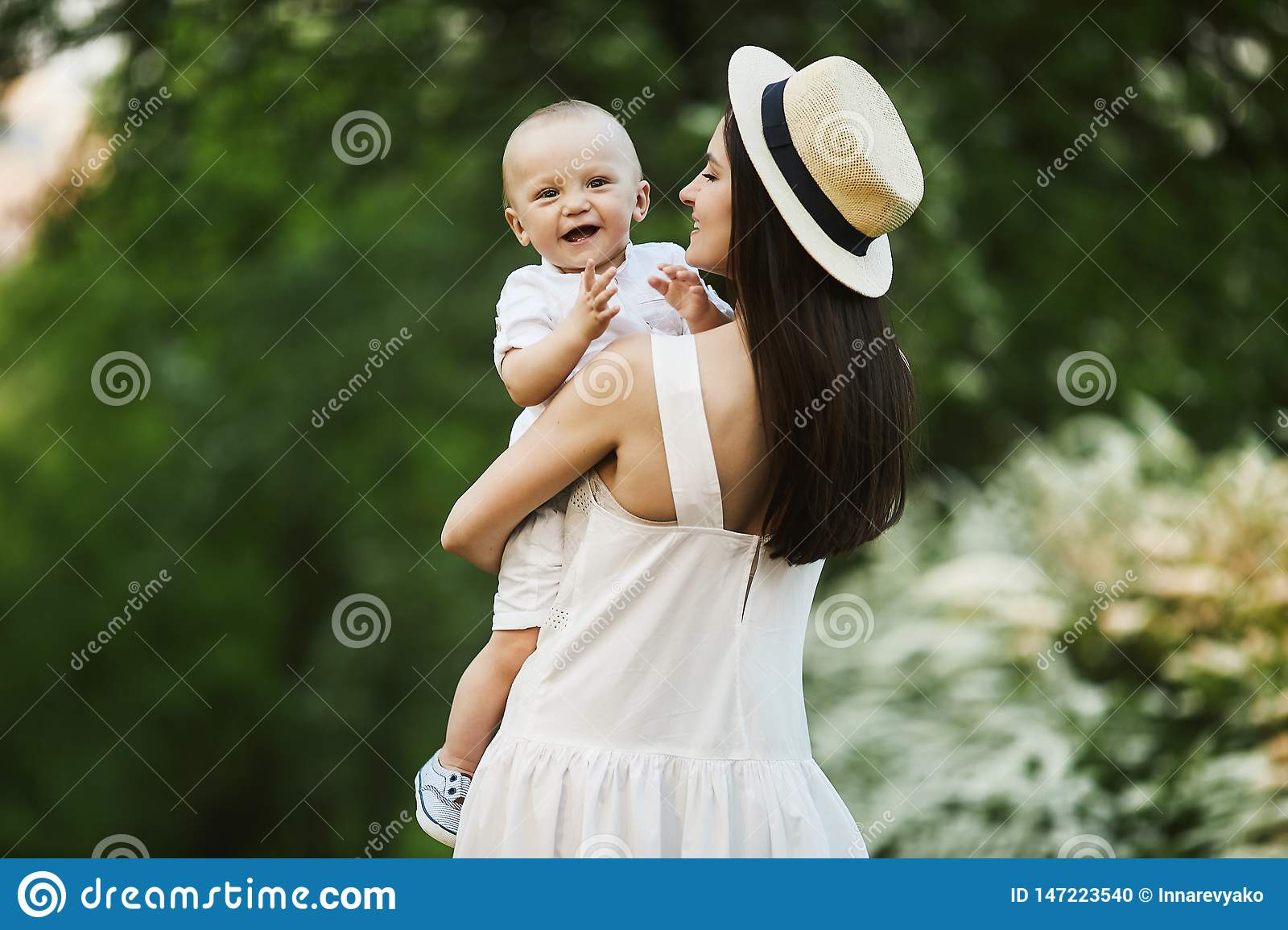 Beautiful young woman in the stylish hat and in a white dress with her cute little son in shirt and shorts on her hands