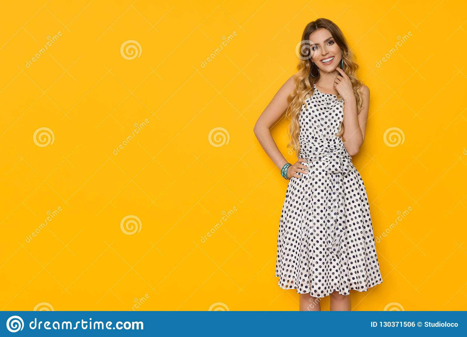 8861cec12eb1 Beautiful young woman in white dotted summer dress is posing with hand on  hip